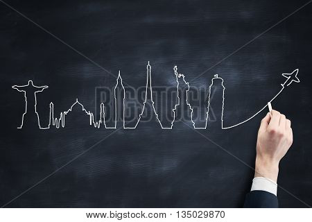 Travel concept with businessman drawing sketch on blackboard background