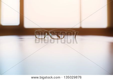 Backlit glasses on bright desktop with window in the background