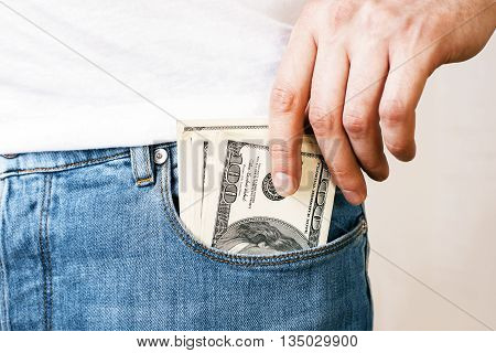Man Putting Money In Pocket