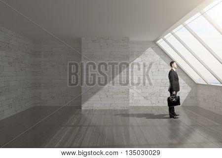 Businessman holding briefcase in empty loft interior with brick wall cocrete ceiling dark wooden floor and window. 3D Rendering