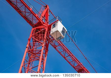 Red industrial construction crane against blue sky in Germany
