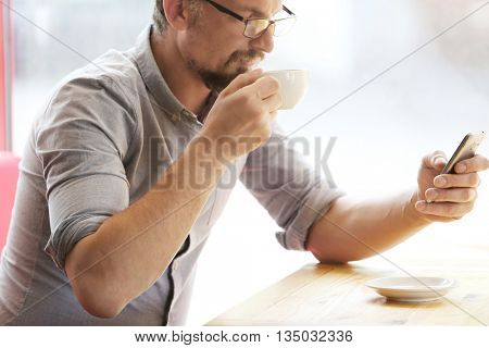 Businessman with cellphone and cup of coffee in cafe