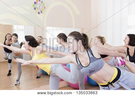 Sport and Healthlife Concepts. Group of Five Young Caucasian Females Making Stretching Exercises in Sport Class.Horizontal Image Orientation