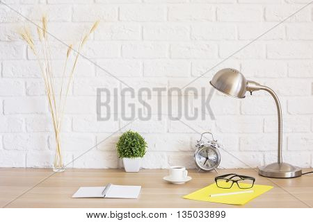 Creative desk with glasses alarm clock notepad coffee cup wheat spikes and other items