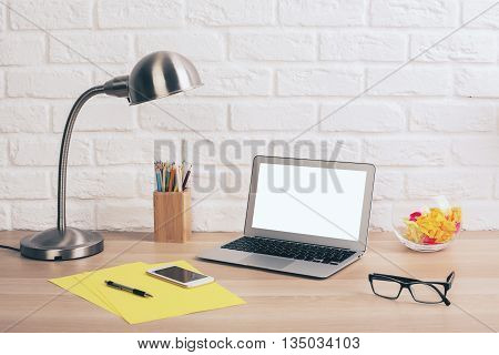 Creative designer desktop with blank white laptop stationery items table lamp glasses and smartphone on white brick wall background. Mock up