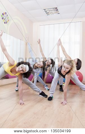 Group of Five Professional Sportswomen Making Stretching Exercises with Trunk Bending in Sport Class. Vertical Shot