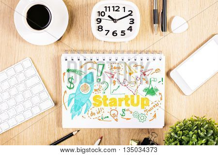 Start up concept with rocket ship sketch on notepad placed on wooden office desktop with stationery items coffee cup and blank white smartphone. Mock up