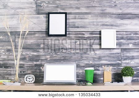 Creative designer table with blank white laptop clock coffee and other items with picture frames hanging above on wooden wall. Mock up