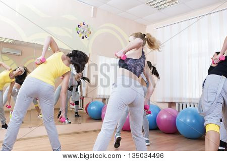 Sport and Fitness Concepts. Five Professional Sportswomen Having Trunk Bending Exercises with Barbells. In Sport Class with Fitballs Around. Horizontal Image