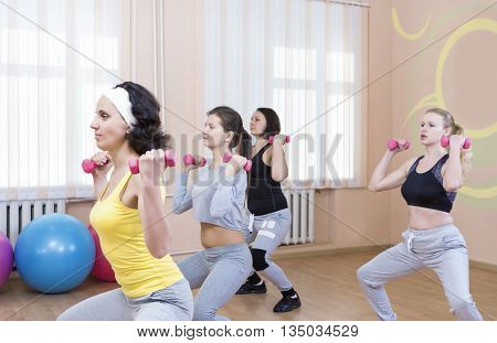 Sport and Fitness Concepts. Five Professional Sportswomen Having Trunk Bending Exercises with Barbells. In Sport Class with Fitballs Around. Horizontal Shot