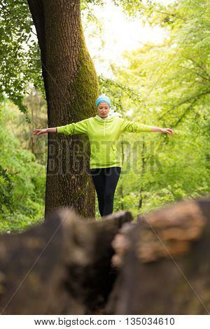 Active sporty woman holding balance on tree trunk while workout in nature. Wellness and healthy lifestyle concept.
