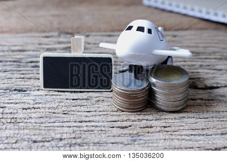 concept idea money save for travel coin and plastic airplane with empty small wooden for text