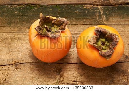 two delicious orange persimmon on an old wooden table