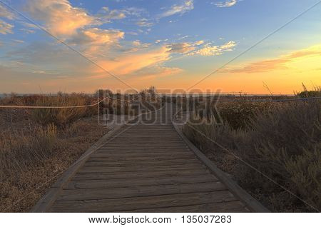 Boardwalk at Crystal Cove beach in California at sunset in the summer