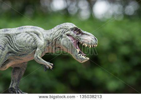 a tyrannosaurus toy in front of trees