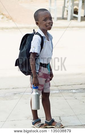 A small schoolboy waiting for a school bus
