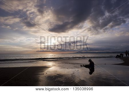 Depressed woman is a silhouette of a sad and isolated woman sitting on the beach while those around her have fun and enjoy life.