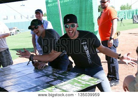 ARLINGTON, TX - APR 18: Recording artists Justin Moore (L) and Luke Bryan sign posters at the ACM & Cabela's Great Outdoor Archery Event at the Texas Rangers Youth on April 18, 2015.