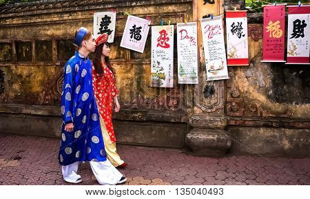 HAI DUONG, VIETNAM, February 11, 2016 young couples, dressed in traditional dress, walk the old town, many calligraphy. Downtown Hai Duong, Vietnam, Tet