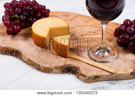 Close up of sliced gourmet cheese with red wine and grapes on wooden server in background. Selective focus on front of cheese wedge.