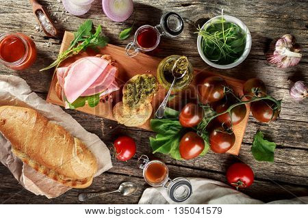 Baguette, ham and vegetables. Appetizers on wooden cutting Board. Top view