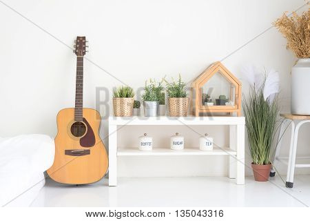 Cozy corner in living room in modern and stylish design. Guitar is on the left side of the image and table with small green trees are on the right side of the image.