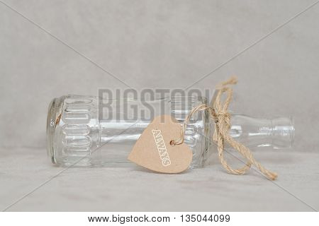 Empty bottle with heart shape tag and ribbon.  ALWAYS word on tag