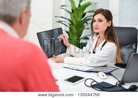 Doctor speaking to her patient while showing an x-ray