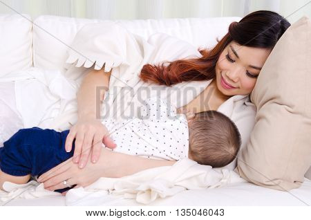 Beautiful asian woman breastfeeding her six months old baby boy