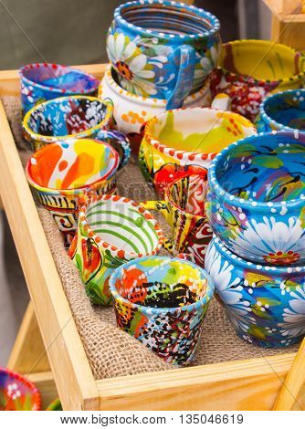 Collection of colorful cups and bowls for sale on stall at the bazaar kitchen accessories