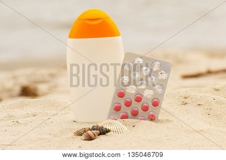 Shells sun lotion and pills of vitamin E on sand at the beach seasonal concept and successful tanning
