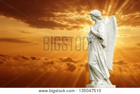 Beautiful angel over yellow magical sky with rays of light