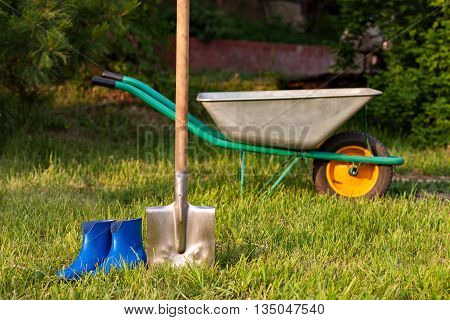 Bright inventory gardener. Blue rubber boots on a background of green lawn. Trolley and shovel for the garden care.