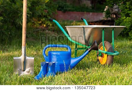 Blue watering can and rubber boots on a background of green lawn. Trolley and shovel for the garden care. Bright inventory gardener.