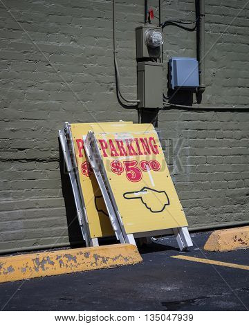 Two folding parking signs against a brick wall