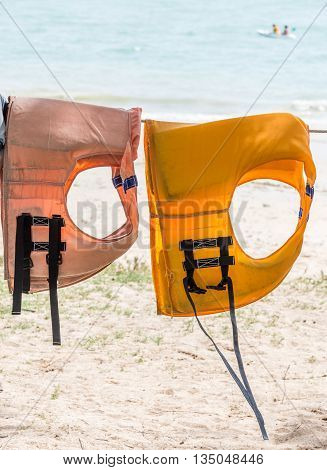 Double life jacket is hanging for rent near the sea.