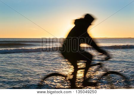 Cyclist in blurred motion sillouette on Papamoa Beach outlok to horizon beautiful glow into into sunrise