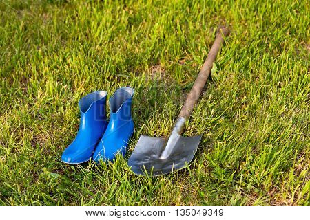Blue rubber boots on a background of green lawn. Bright gardener tools for garden care.