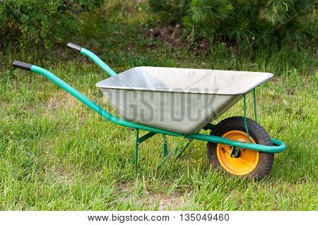 Wheelbarrow on grass against the background of the setting sun. Bright gardener tools for garden care.