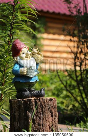 Little garden gnome figurine standing on a tree stump in the backyard