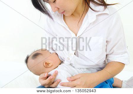 Asian mother breastfeeding her cute baby boy