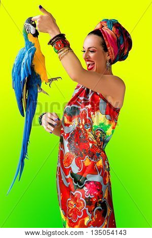 Portrait of young laughting attractive woman in african style with ara parrot on her finger on colorful background
