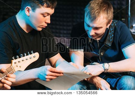 Musicians learn text, explaining moment. Guy explains to the guitar player his part in the song. Guitarist learn new notes
