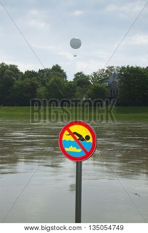 Poland Kraków flooded Vistula/Wisła river embankments no swimming sign over the water sightseeing baloon in the background