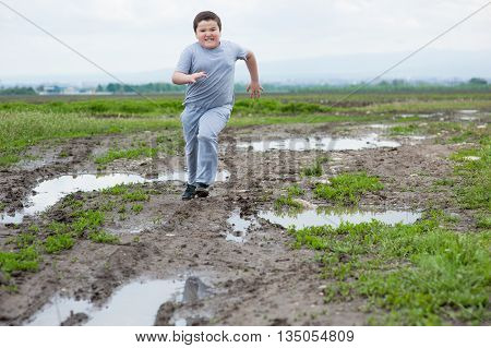 fat boy running in the field among the mud and puddles