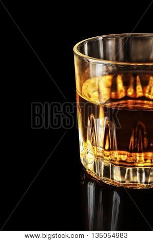 Part of a glass with alcohol on a black background. The object is located a shot on the right. Part of object. Reflection from a surface. Indoors. Vertical format. Color. Photo.