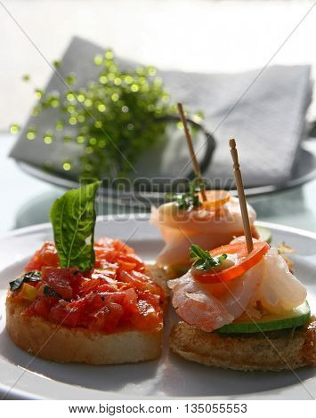 Canape juicy tomatoes shrimp on fresh bread pesto as topping (selective focus at front)