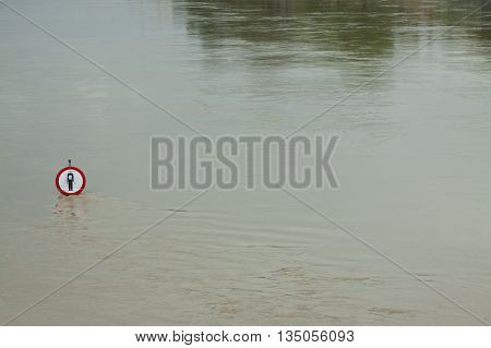 No entry sign on a flooded river embankment