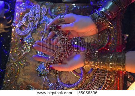 Golden Shiny Oriental Jewelry and Accessories: Female Hands with beautiful National Indian Jewellery Eastern Fairy Tale (Harem) Wedding Luxury Fashion and Beauty. Traditional Sari clothes details. Color lenses