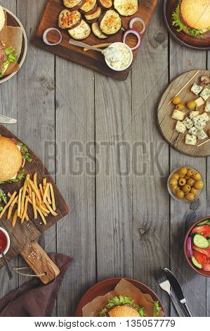 Different food on a wooden table burgers fries grilled eggplant salad sauces roquefort cheese and olives top view with copy space. Outdoors food Concept